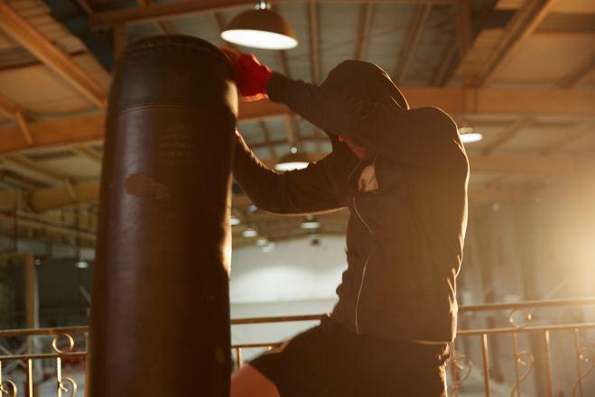 man kneeing a boxing bag