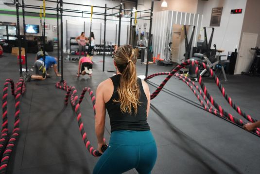 girl working out with battle ropes