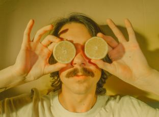 person holding lemons on their eyes