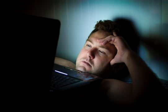 man laying in bed late night working