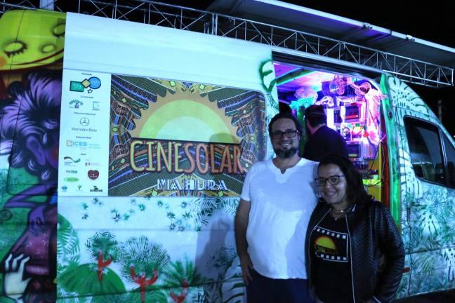 Foto mostra duas pessoas em frente da van do Cine Solar