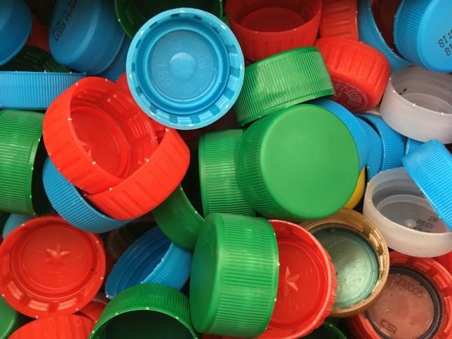 Foto mostra várias tampinhas de plástico de garrafas pets, de diversas cores