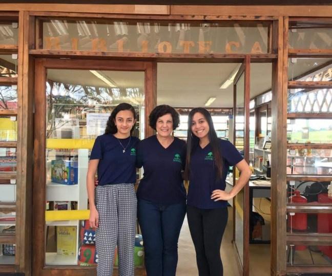 Foto mostra três colaboradoras em frente da Biblioteca do Centro Max Feffer de Cultura e Sustentabilidade
