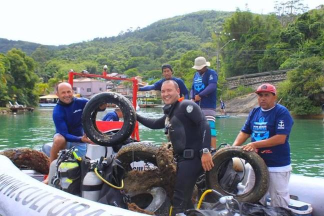 Foto mostra pessoas em bote, após coleta de lixo do mar, em Florianópolis