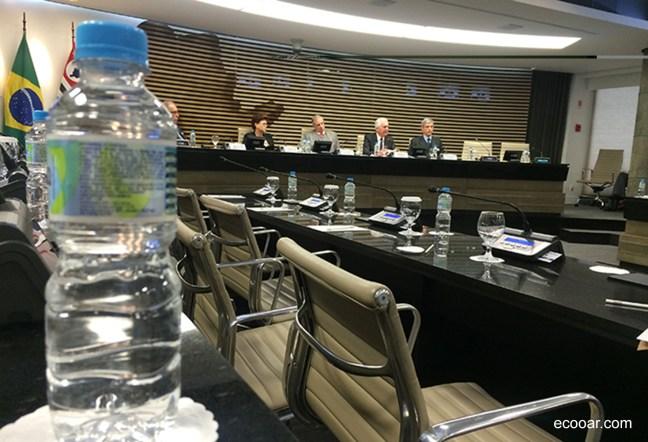 Foto mostra auditório de reunião da FIESP/CIESP e garrafa de água em primeiro plano