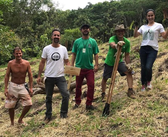 Foto mostra mostra pessoas após plantio de árvores em Florianópolis