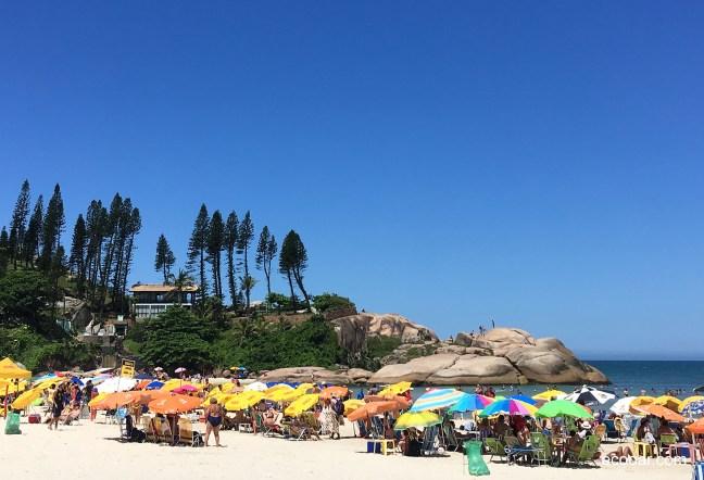 Foto mostra Praia da Joaquina, com grande quantidade de guarda sóis e uma casa no morro