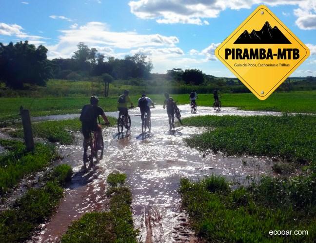 Foto mostra logo do Piramba MTB e integrantes do grupo pedalando cada um uma bike em uma área com barro
