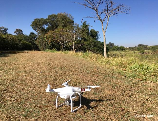 Foto mostra drone pousado em gramado com árvores ao fundo