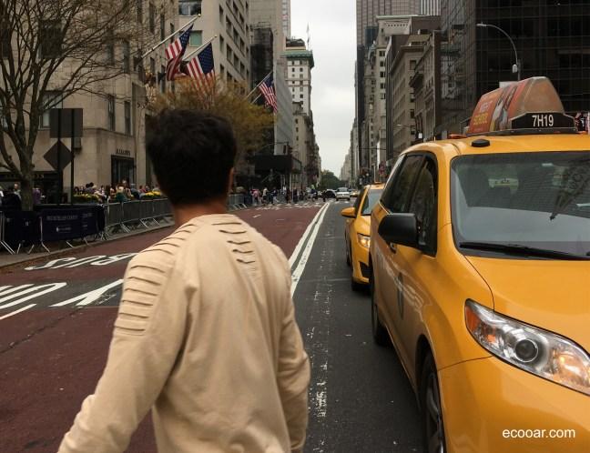 Foto mostra Nova York, pedestre atravessando rua principal e táxis afetados pela economia