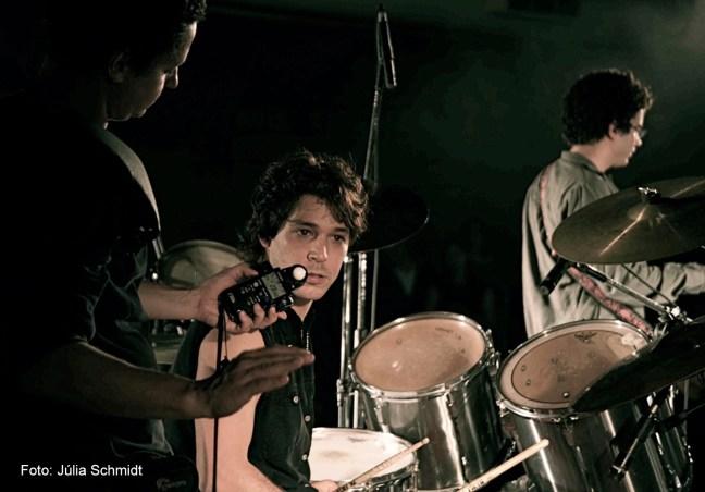 Foto mostra o ator Bruno Torres sentado em frente a uma bateria