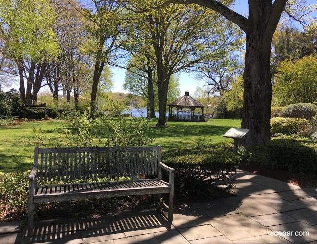 Foto mostra banco de madeira, árvores e coreto no jardim em Essex Park, Connecticut