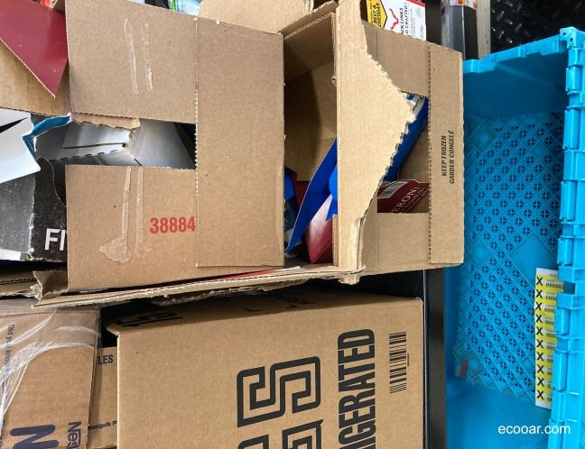 Foto mostra caixas de papelão empilhadas por colaborador de empresa