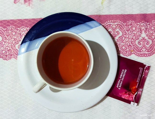 Foto contém uma xícara, cheia de chá de rosa vista de cima, sobre uma mesa