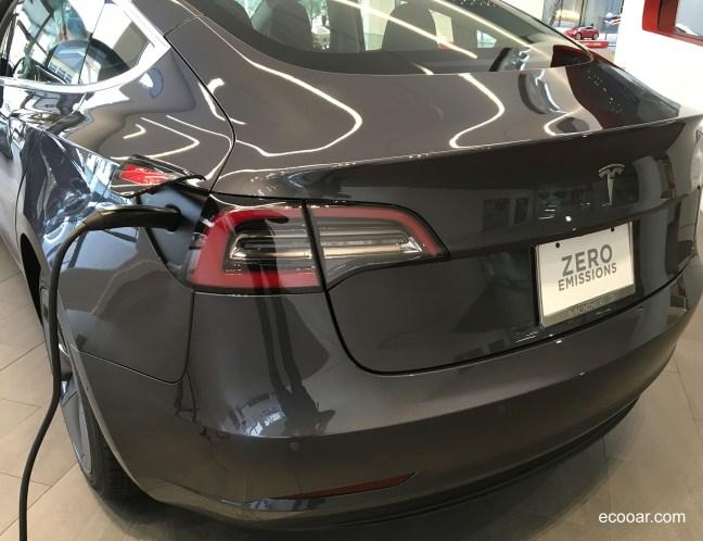 Foto mostra parte traseira do carro Tesla com a placa escrita Zero Emissions