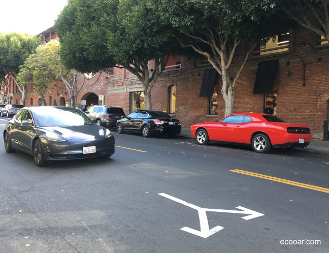 Foto mostra carros em uma rua arborizada