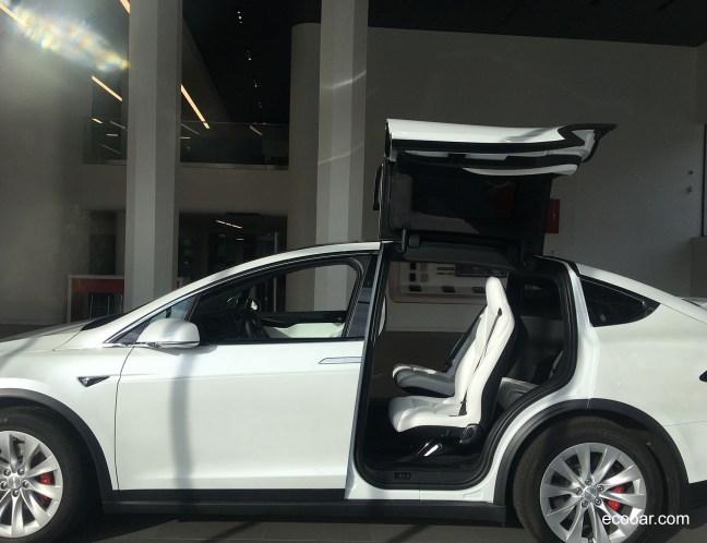 Foto mostra carro Tesla Model X com as portas traseiras abertas para cima
