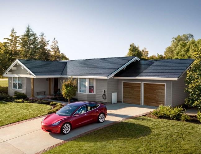 Foto mostra telhado com tecnologia de painéis solares com carro Tesla na frente