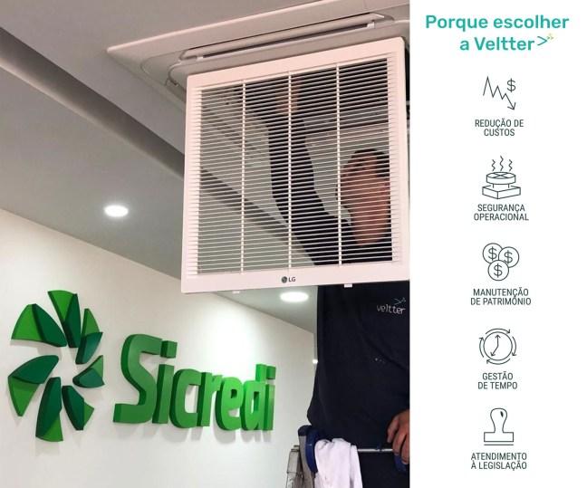 Foto mostra técnico limpando ar condicionado, com letreiro Sicredi ao fundo