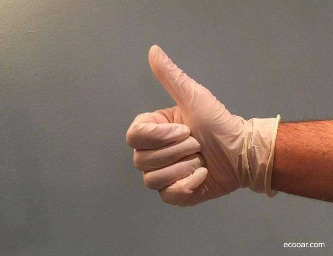 Foto mostra uma mão com luva plástica fazendo sinal de positivo/like