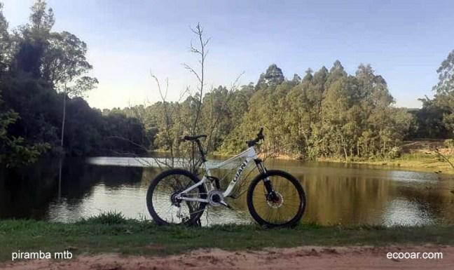 Foto mostra uma bicicleta com um lago e uma floresta ao fundo