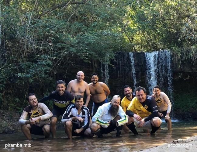 Foto mostra pessoas em uma mata com uma cachoeira ao fundo