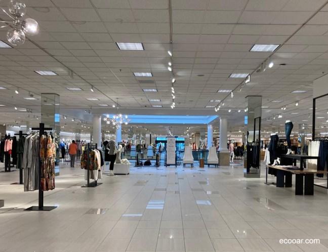 Foto mostra loja de departamentos com roupas em cabides