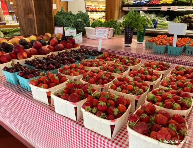 Foto mostra cestas com morangos e cerejas sobre uma mesa em um mercadinho
