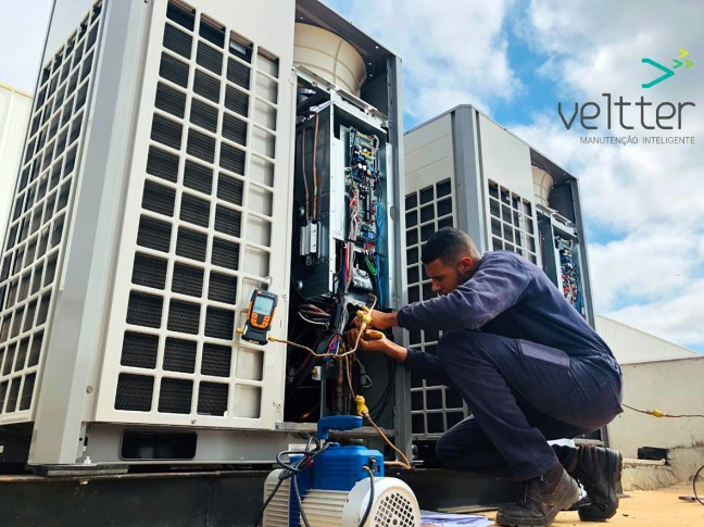 Foto mostra técnico dando manutenção em ar condicionado no telhado de empresa