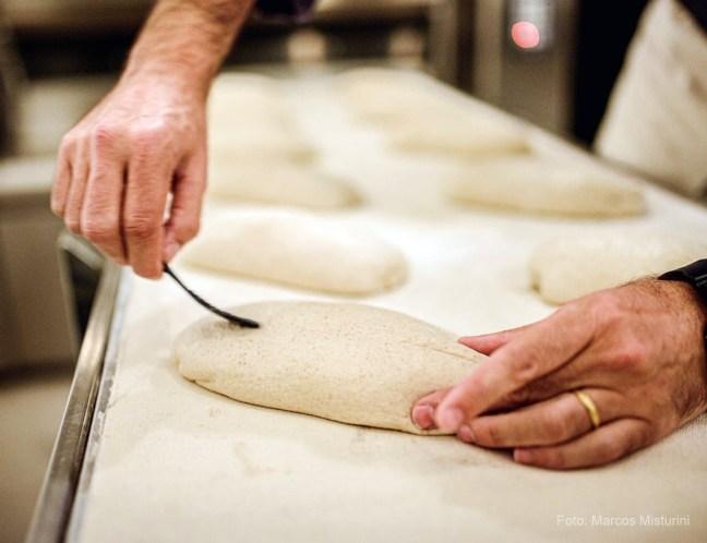 Foto mostra padeiro finalizando um pão