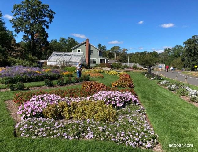 Foto mostra jardineiro ao fundo, com jardim em Elizabeth Park Conservancy, em Connecticut nos EUA