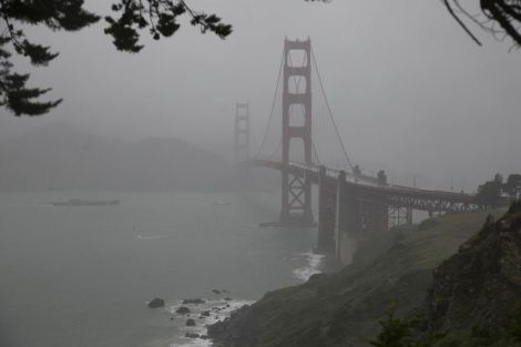 The Golden Gate Bridge is seen through rain and mist. Photograph by Anand Varma