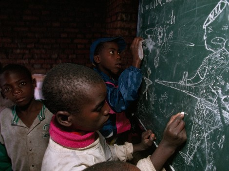 """A Hutu boy, orphaned by the war in Rwanda, draws pictures of Tutsi-led Rwandan Patriotic Front soldiers shooting small stick figures who represent Hutus. Many Rwandan Hutus think their role in the Rwandan civil war is being re-written in an """"official narrative"""" school curriculum. Photograph by Michael Nichols, National Geographic"""