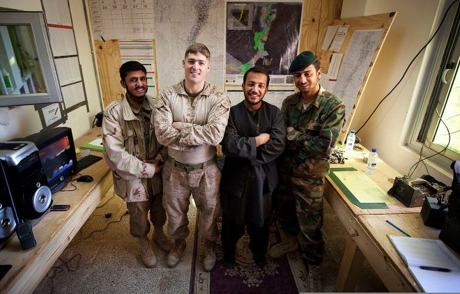 Organizing military and police work in Afghanistan was one of the evolving goals of U.S. military forces in Afghanistan. Here, U.S. Marine Corporal Nathan Dittmer (second from left) smiles with his Afghan coworkers in Garmsir district, part of Helmand Province: Police patrolman Hazrat Ali, Afghan National Directorate of Security 1st Lt. Maiwand Salim; and Afghan National Army Sgt. Anamullah Photograph by Corporal Reece Lodder, courtesy Wikimedia.