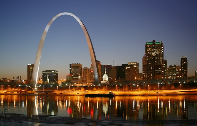 Bright arch, big city . . . St. Louis and the Mississippi River glisten in the gloaming (look it up). Photograph by Daniel Schwen, courtesy Wikimedia. CCY-BY-SA-4.0