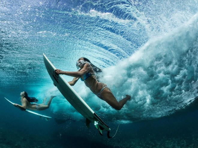 to youth . . . Best friends dive under a wave on their way to a surfing spot near their hometown of Makaha. Photograph by Paul Nicklen, National Geographic