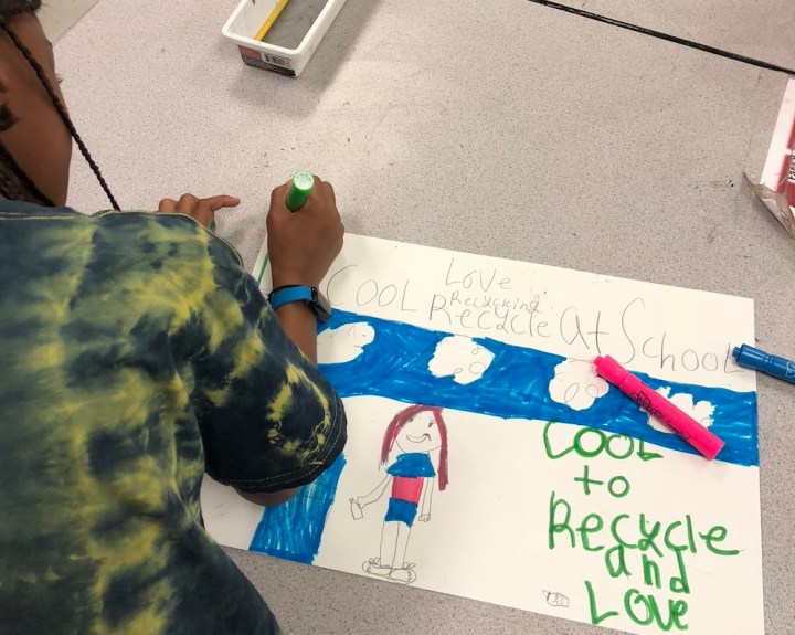 A student illustrates a poster about recycling at school