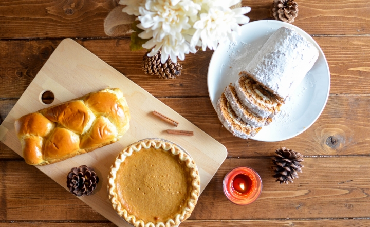 Bread and pie on wooden board and white plate on wood table with pinecones
