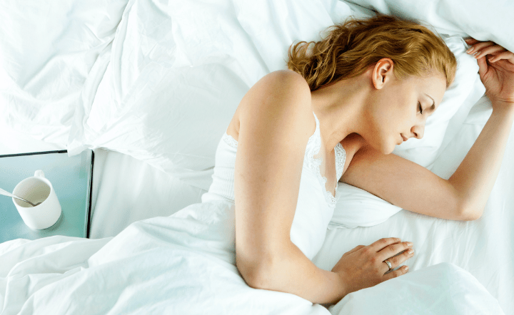 Woman wearing white clothing sleeping in bed
