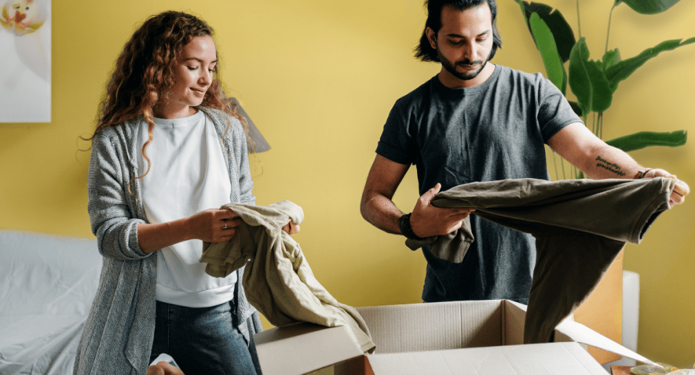 Man and woman holding clothes with moving boxes