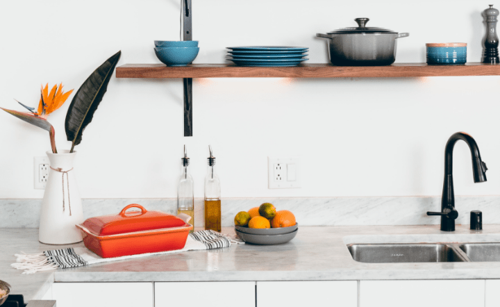 Blue ceramic dinnerware on wooden rack and fruits, vase, and oven pot on kitchen counter by the sink