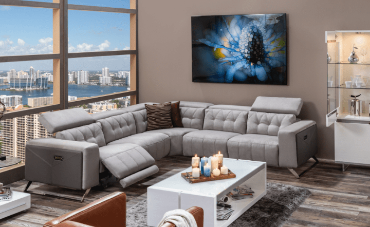 Gray fabric sofa with gray rug, white bar cabinet, white coffee table and side table, blue wall art, and brown leather chair in lifestyle setting by El Dorado Furniture