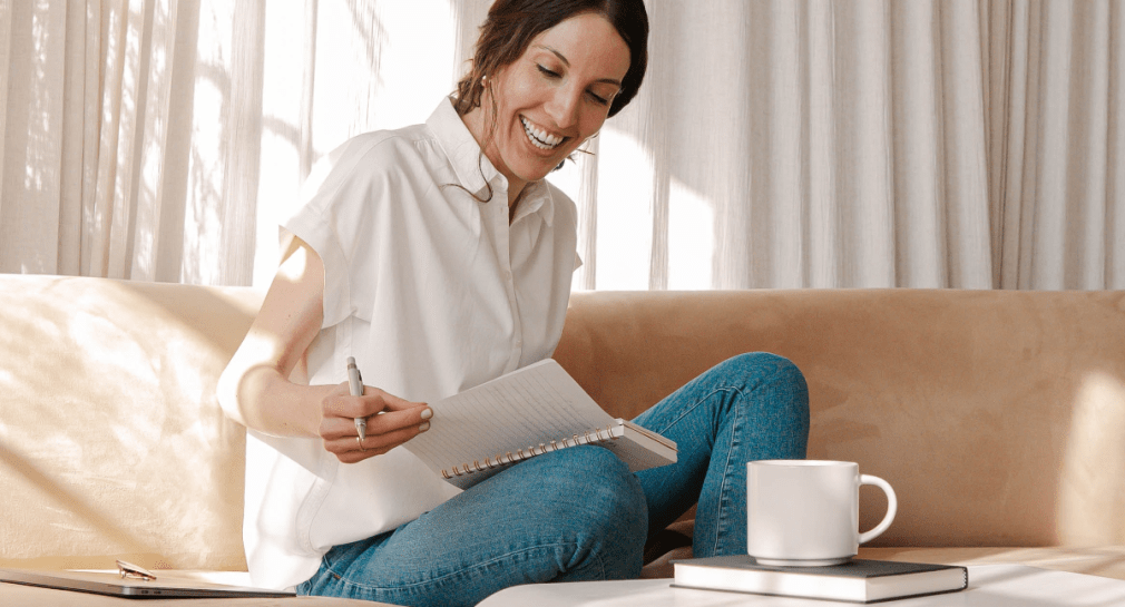 Woman in white shirt and blue jeans sitting on tan sofa writing in notebook