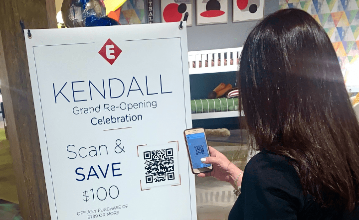 Woman in black jacket scanning a QR code onto her mobile device from a standee in a showroom setting by El Dorado Furniture.