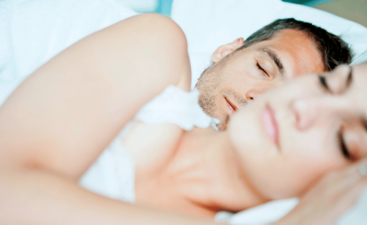 Man and woman in white tank top sleeping in bed