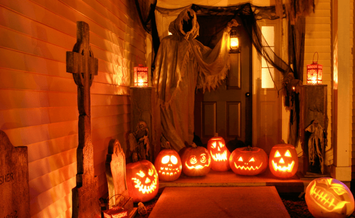 At night, an eerie front porch is illuminated by jack-o-lanterns with tombstones along the walkway and a giant grim reaper figure hovering over the door.