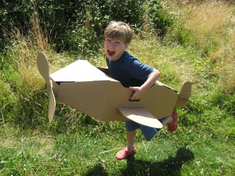 menino se divertindo com avião feito de papelão nas férias