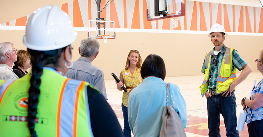 a man in a hard hat addressing a tour in a basketball court