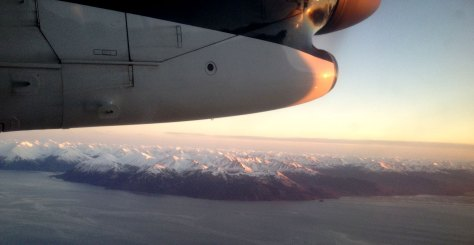 Part of airplane wing over Alaskan coastline