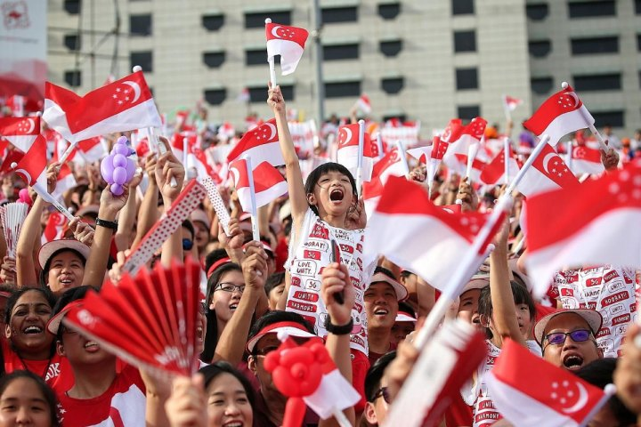 crowd waving Singapore flags